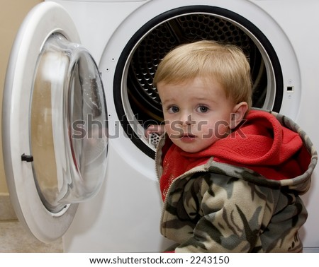 Young cute boy doing the laundry at home - stock photo
