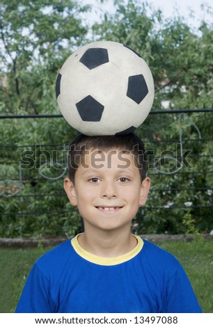 Young cute boy holding a soccer ball over his head - stock photo