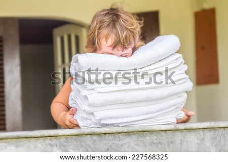 young cute child girl holding rolled beach or spa towels on outdoor house terrace - stock photo