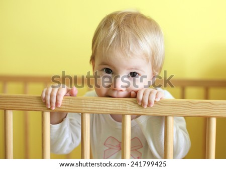 Young cute child in crib - stock photo