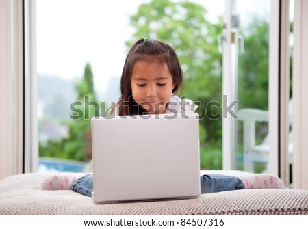 Young cute child using a computer in an indoor living room setting with large window - stock photo