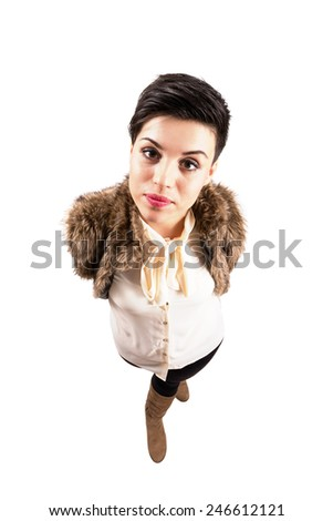 Young cute confident woman in winter clothes staring at camera.  High angle view wide lens full body length portrait isolated over white background. - stock photo