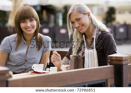 young cute elegant woman sitting outdoor in a cafe in a city with coffee and smiling - stock photo
