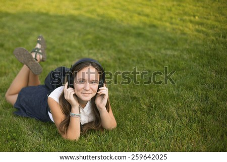 Young cute girl enjoying music with headphones while lying in the grass. With space for text. - stock photo