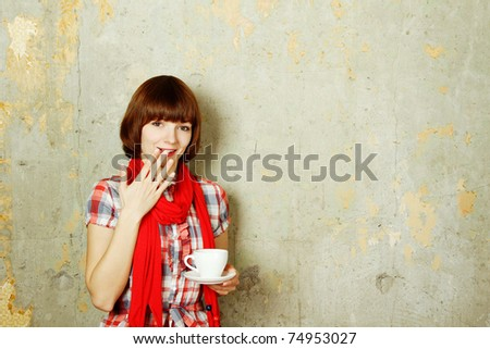 Young cute girl in a checkered red dress against a background of an old concrete wall drinking coffee from a white cup - stock photo