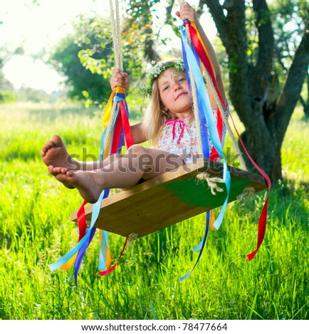 Young cute girl on swing with ribbons in the garden