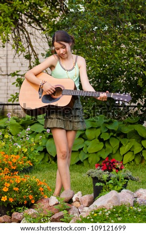 Young cute girl playing guitar and singing in garden near flowers - stock photo
