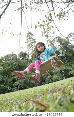 Young cute girl playing swing in the park. - stock photo