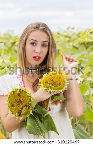 Young cute girl posing in sunflower field - stock photo
