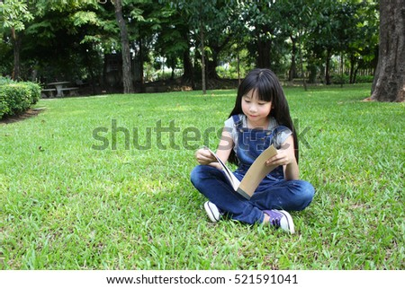 Young cute girl reading in the park