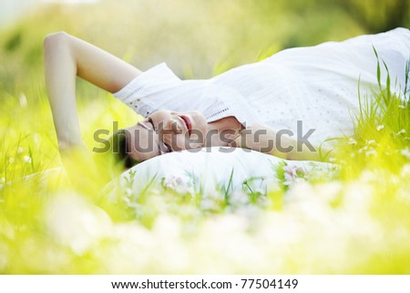 Young cute girl resting on soft pillow in fresh spring grass - stock photo