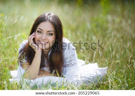 Young cute girl resting on soft pillow in fresh spring grass. Young woman sleeping on soft pillow in fresh spring grass.
