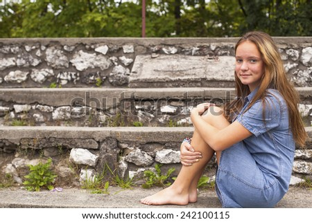 Young cute girl sitting on the stone steps in the historic park. - stock photo