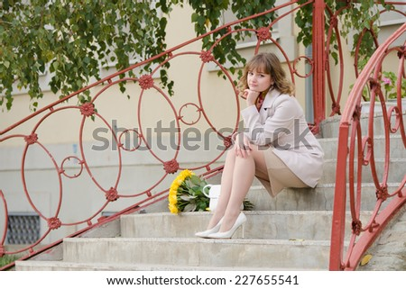 Young cute girl with a bouquet of yellow roses walks in autumn cool weather