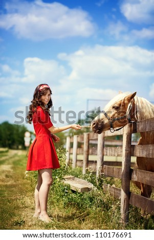 Young cute girl  with horse on farm