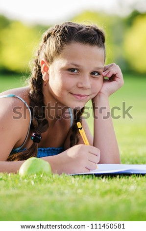 Young cute girl writing into her notebook in the park - stock photo