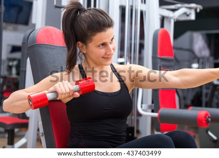Young, cute, healthy, active trainer girl portrait with weights/ dumbbells in her hand resting and playing after a strong workout at the gym. - stock photo