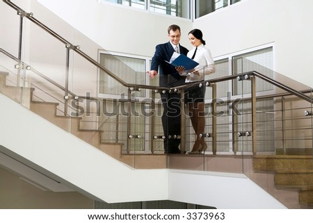 Young cute Hispanic businesswoman showing documents to her colleague on stairs in the office building - stock photo