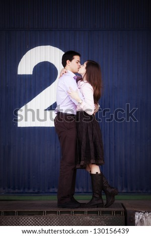 Young cute kissing couple on industrial background. - stock photo