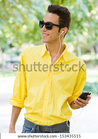 Young cute male listening music on the park with yellow shirt - stock photo