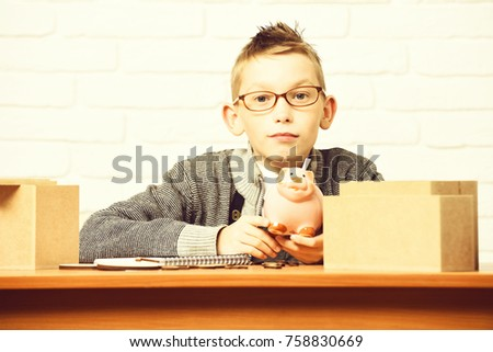 young cute pupil boy in grey sweater and glasses sitting at desk with pink piggy pig bank and copybook in classroom on white brick wall background