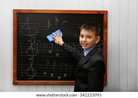 Young cute schoolboy cleaning the blackboard with musical notes - stock photo