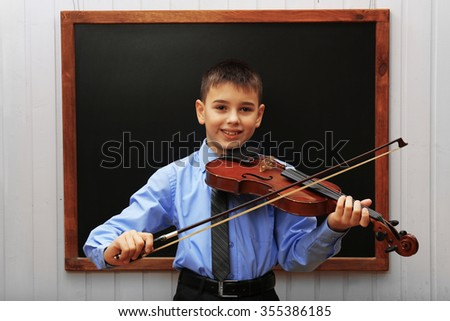 Young cute schoolboy playing the violin at the blackboard - stock photo