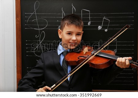 Young cute schoolboy playing the violin the blackboard with musical notes - stock photo