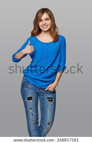 Young cute smiling emotional girl giving you thumb up, over gray background - stock photo