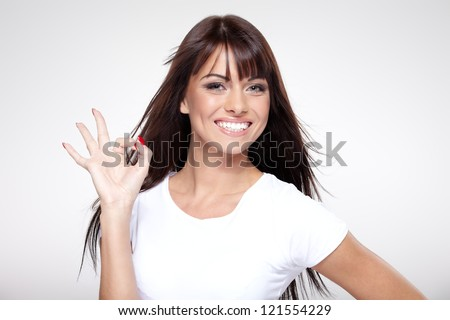 Young cute smiling girl showing OK sign on gray - stock photo