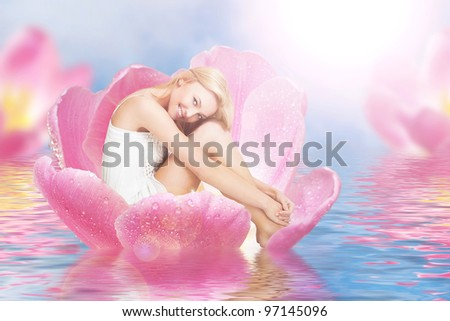 Young cute woman as thumbelina sitting in tulip - stock photo
