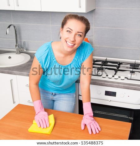 young cute woman cleans the kitchen at her home - stock photo