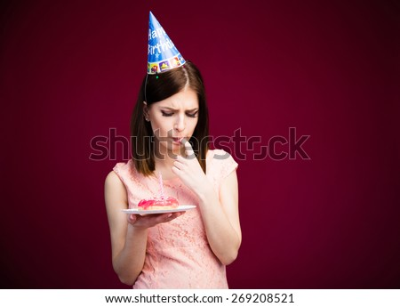 Young cute woman holding donut with candle over pink background - stock photo