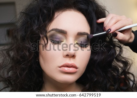 Young cute woman in beauty salon on make-up.