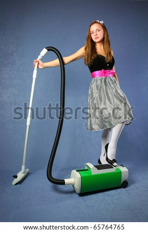Young cute woman in bright dress with hoover stands over blue background - stock photo