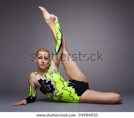 Young cute woman in gymnast suit doing split