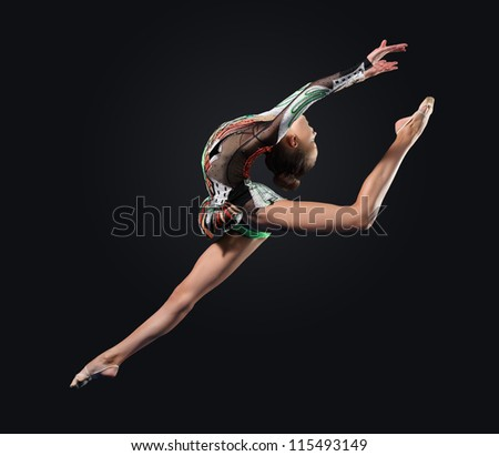 Young cute woman in gymnast suit show athletic skill on black background - stock photo