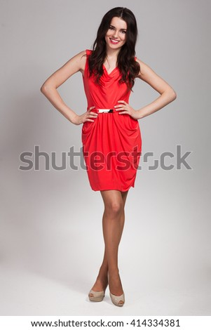 Young cute woman in red posing on gray background