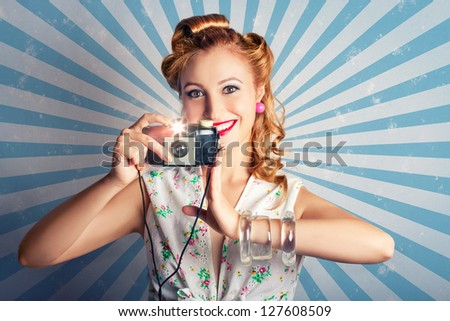 Young Cute Woman In Sixties Fashion Style Smiling When Holding An Instant Camera While Pressing The Shutter Button In A Classic Capture Concept On Blue Starburst Background - stock photo
