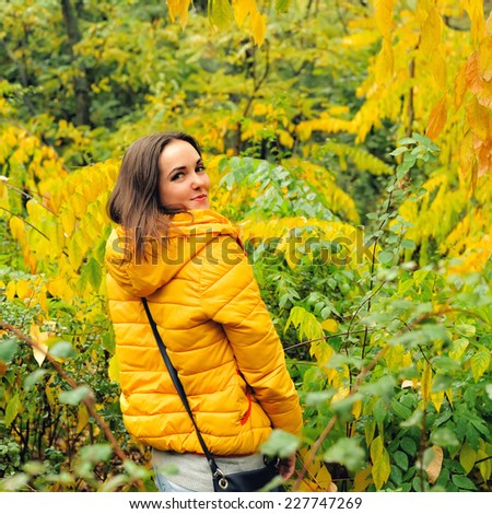 Young cute woman in yellow hoody walking in autumn forest. - stock photo