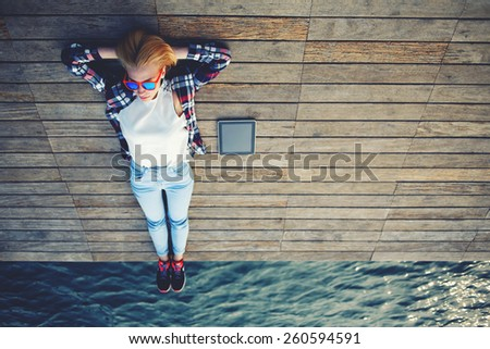 Young cute woman lying on a wooden jetty enjoying the sunshine, tourist girl in bright summer glasses lying on jetty by river,vintage photo of relaxing young woman in nature with tablet, cross process - stock photo