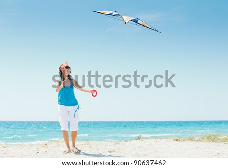 Young cute woman playing with a colorful kite on the tropical beach. - stock photo