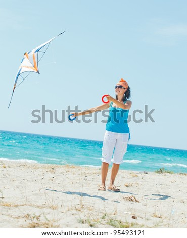 Young cute woman playing with a colorful kite on the tropical beach. Vertikal veiw