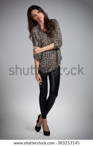 Young cute woman posing on gray background - stock photo