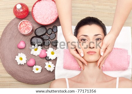 young cute woman receiving a facial massage at spa center - stock photo