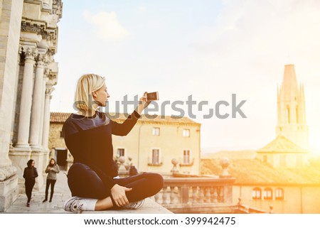 Young cute woman wanderer is making photo with smart phone camera of a beautiful old tower against sunset. Gorgeous female tourist is shooting video of beautiful city landscape on her cell telephone - stock photo