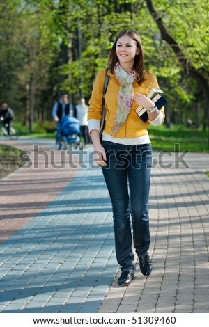 young cute woman with books walking in the park - stock photo