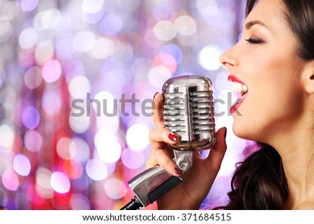 Young cute woman with retro microphone against bright glitter background