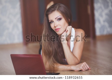 young cute woman working with laptop at home with red apples laying around her - stock photo