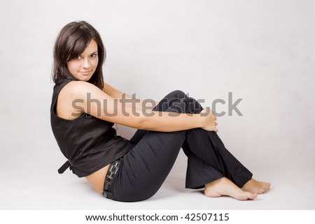 young cute young girl sitting on the floor - stock photo